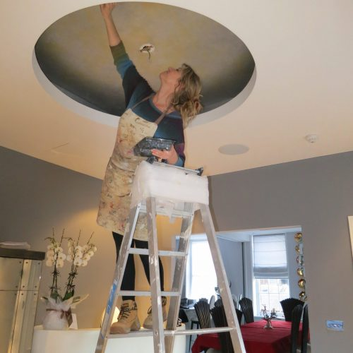 Specialist Decorator Working On Gold And Silver Painted Ceiling